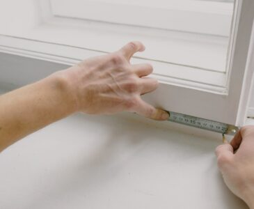 crop worker measuring window frame with ruler