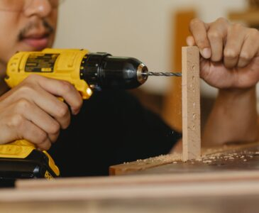 man drilling timber panel with screwdriver on table