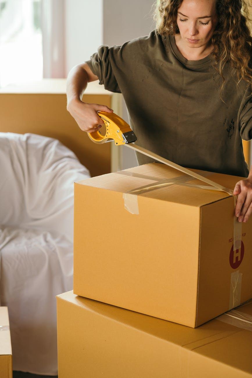 crop woman packing box in bedroom